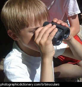 Photo of a child looking through binoculars