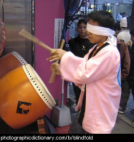 Photo of a boy drumming blindfolded.