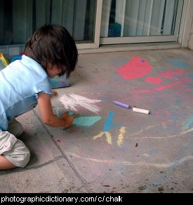 Photo of a child drawing with chalk