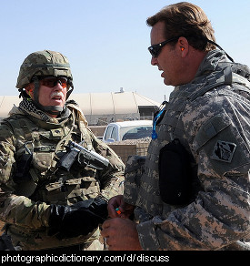 Photo of two men in the army having a discussion