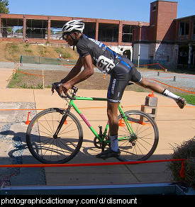 Photo of a man dismounting a bicycle