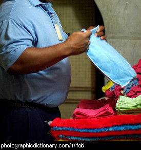 Photo of a man folding clothes.
