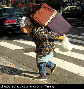 Photo of a woman carrying a heavy load
