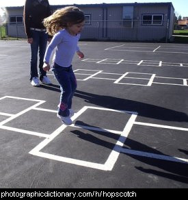 Photo of a child playing hopscotch