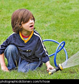 Photo of a boy holding a hose