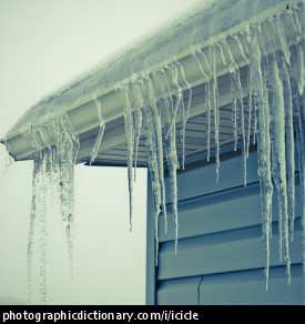 Photo of icicles hanging from the roof of a house.