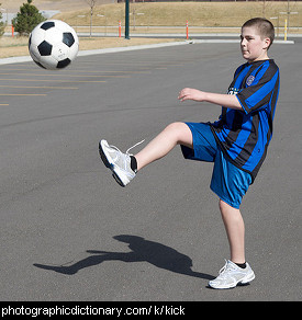 Photo of a boy kicking a ball.