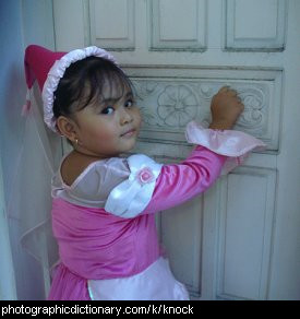 Photo of a little girl knocking on a door