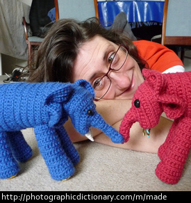 Photo of a woman who made some knitted elephants
