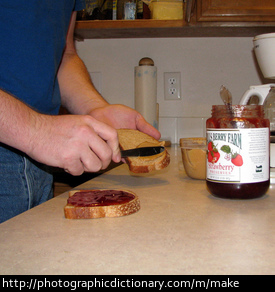 Photo of a man making a peanut butter and jelly sandwich