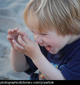 Photo of a child examining some grains of sand