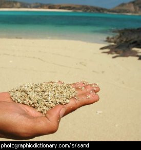 Photo of a hand holding sand