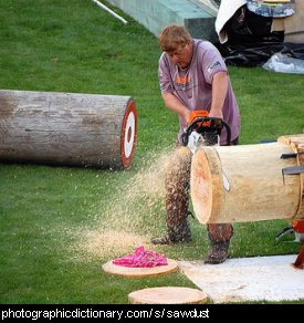Photo of a man making sawdust by cutting wood.