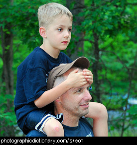 Photo of a boy having a piggyback ride on his father's shoulders