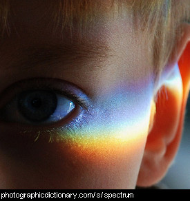 Photo of a boy with a rainbow on his face
