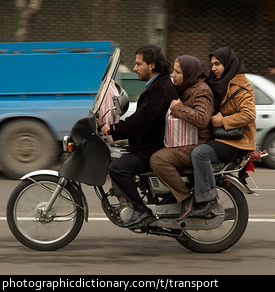 Photo of three people on a motorbike