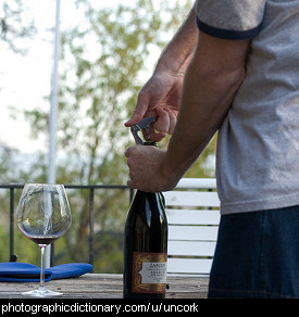 Photo of a man opening a bottle of wine