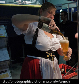 Woman dressed as a wench, serving beer.